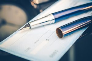 Pen lying on top of checkbook. Paying by checking, credit card and debit card are some of the financing options available with Dalco Heating & Air in Denver area.