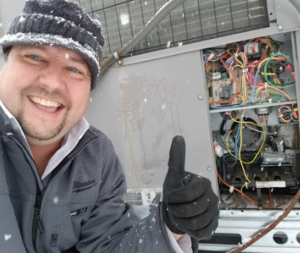 Dalco AC technician at outside electrical panel in the snow outside a Denver area home