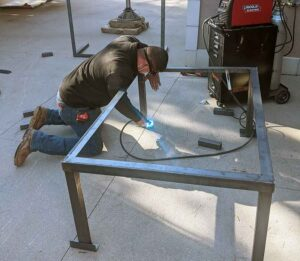AC technician welding frame for air conditioner installation