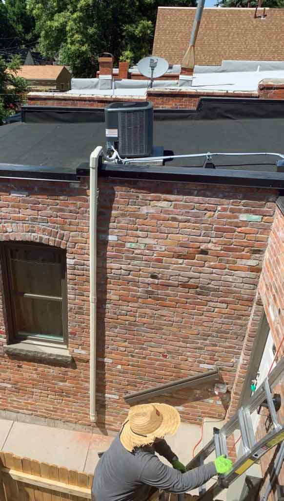 DALCO tech climbing ladder to perform AC maintenance on roof of Denver home